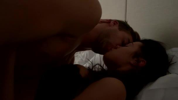 Mann küsst Frau im Bett.