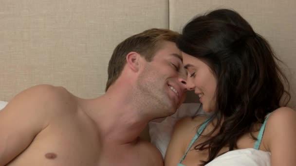 Paar im Bett lächelt.