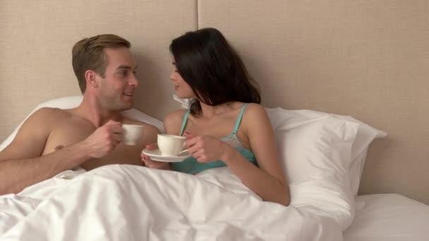 Paar mit Tassen im Bett.