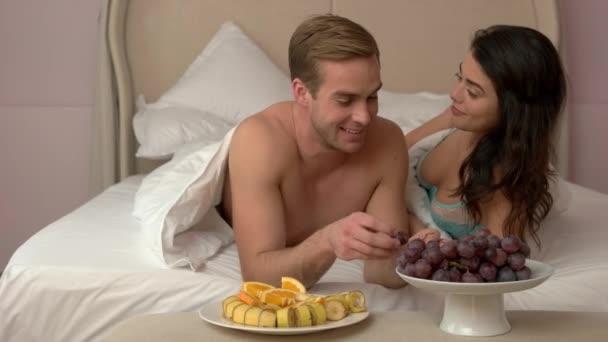 Paar isst im Bett.