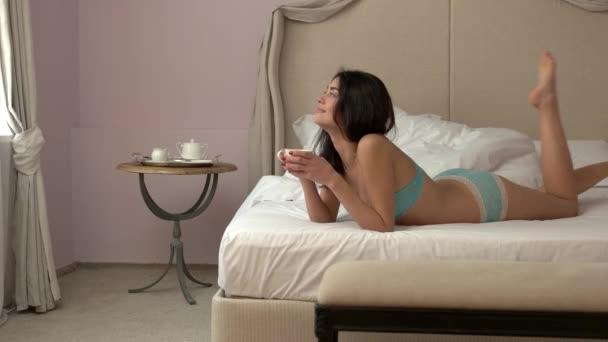 Žena s pohár na posteli.