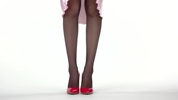 Legs in red heels standing.