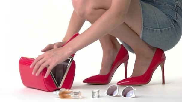 Woman putting things into handbag.