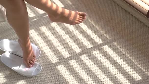 Piedini femminili e pantofole da casa