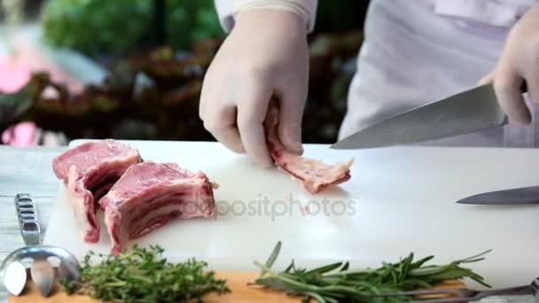 Ruce s nožem a maso.