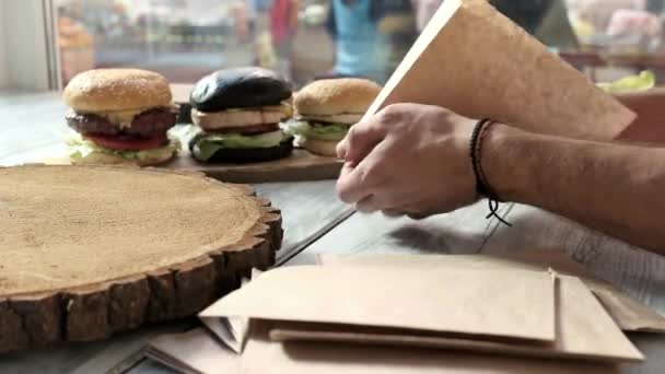 Hands and burger on board.