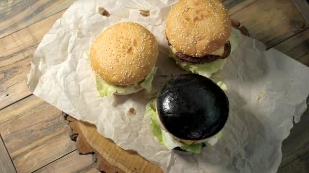 Tři hamburgery na dřevěné pozadí