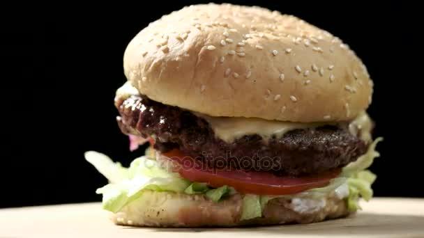 Hamburger close-up na černém pozadí.