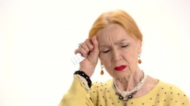 sick elderly woman coughing and holding head on background of