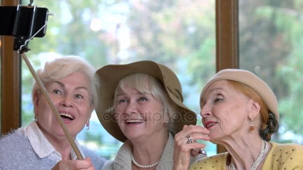 Tři starší dámy užívat selfie.