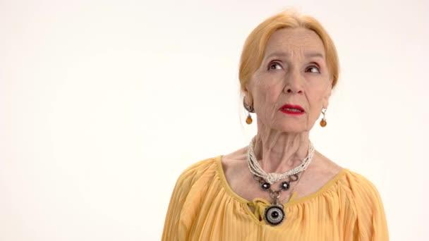 Starší žena ukazuje mlčení gesto
