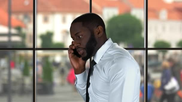 Black man talking on phone.