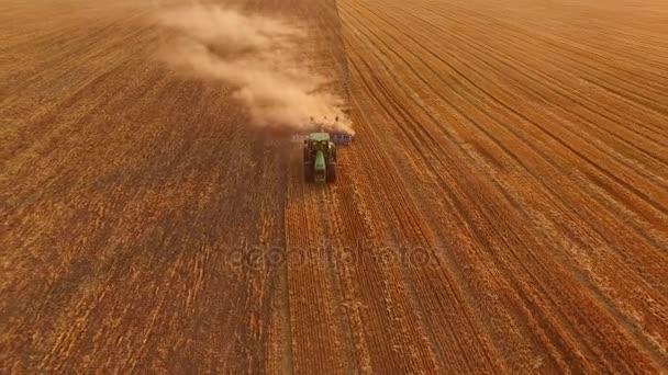 Traktor s pluhem v pohybu.