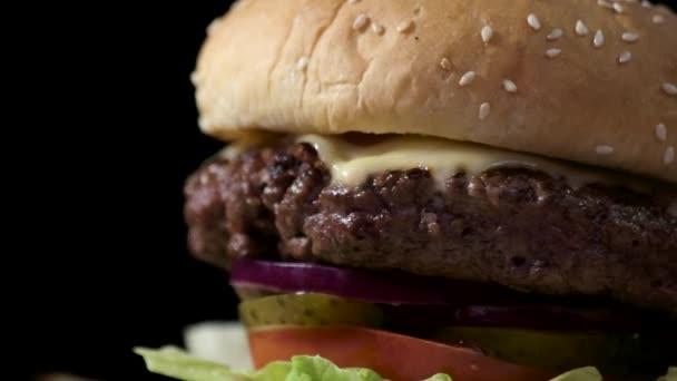 cheeseburger na černém pozadí.