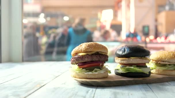 Dřevěná deska a tři hamburgery