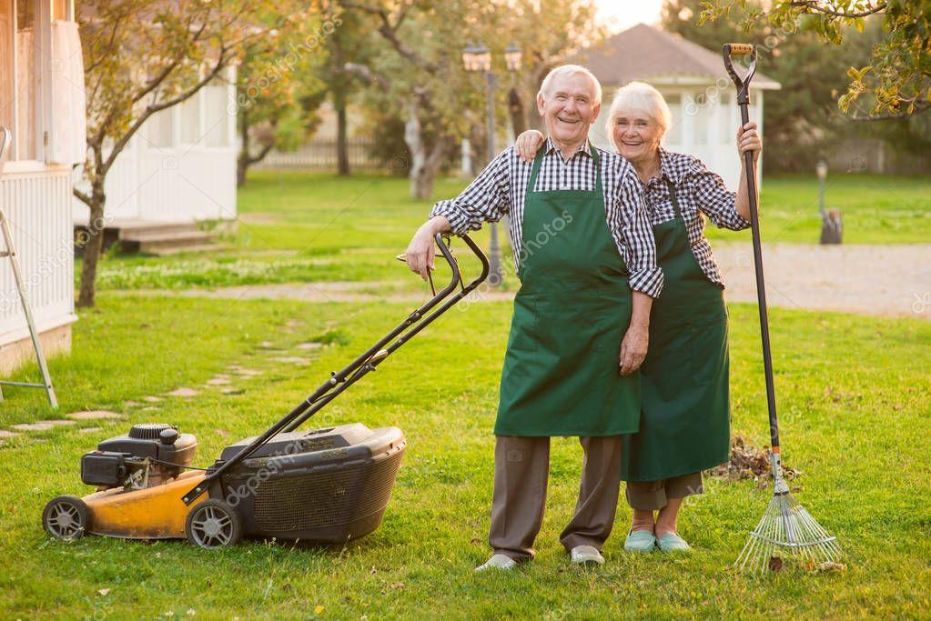 Smiling couple of senior gardeners.