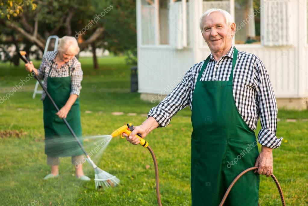 Man with garden hose smiling.