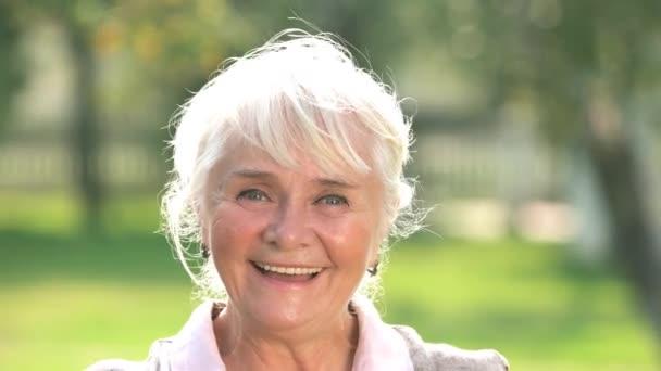 Zamyšleně starší žena s úsměvem