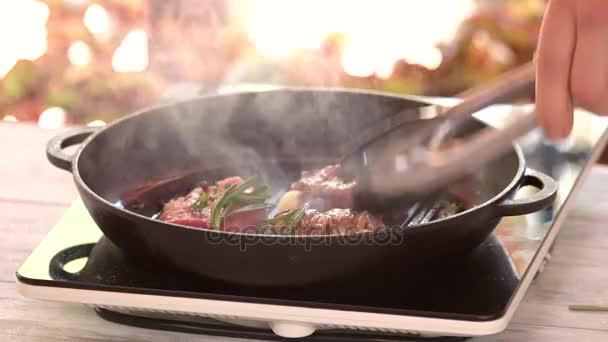 Kleště překlopit steaky v pánvi.