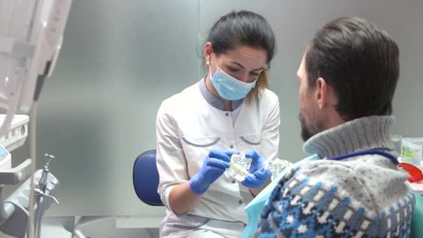 Dentist holding artificial teeth.