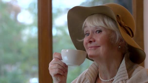 Starší žena s úsměvem a pohár