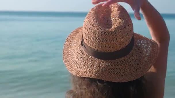 Woman putting on beach hat.