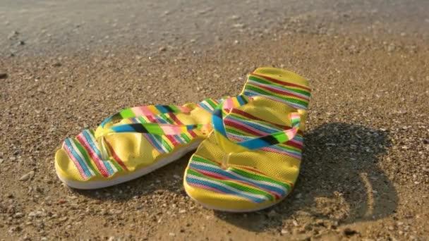 Flip flops on sand background.