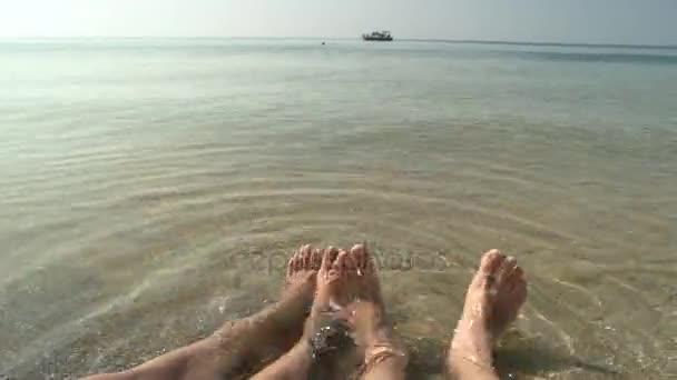 Nohy páru, moře pozadí.