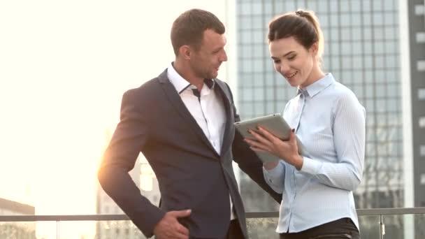 Podnikatel a žena držící tabletu.