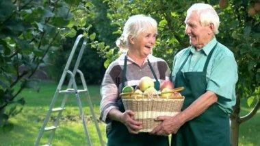 Senior couple holding apple basket.