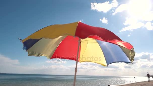 heller Sonnenschirm steht am Strand.