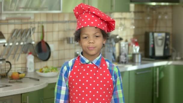 Fröhlicher Junge mit Küchenutensilien
