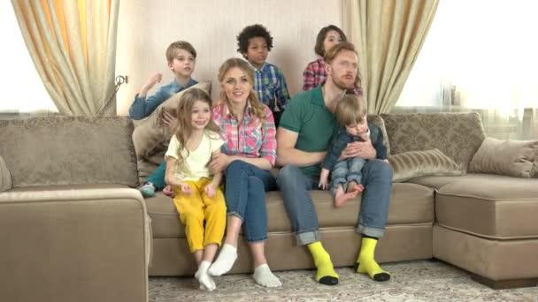 Vzrušený, rodina sedí na gauči.