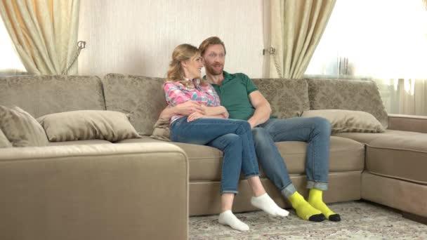Kavkazský pár sedí na gauči.