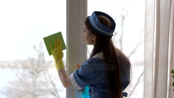 Junge Hausmädchen waschen Fenster