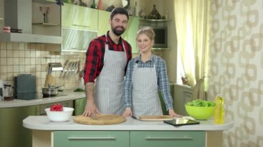 Man and woman smiling, kitchen.