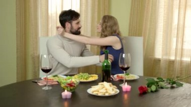 Couple at dinner table hugging.