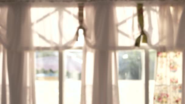 Rozmazané okna se závěsy.