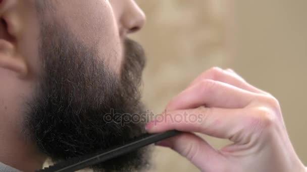 Hand with comb brushing beard.