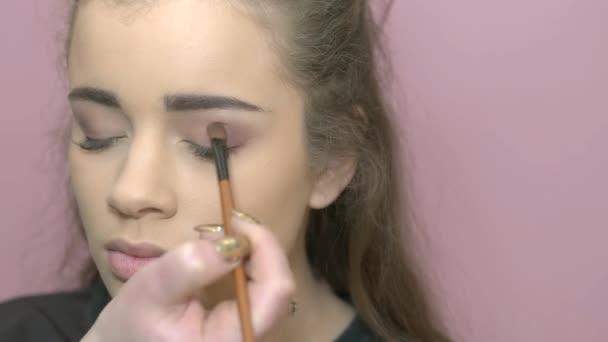 Hand of visagist applying eyeshadow.