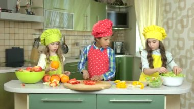 Children cutting vegetables.