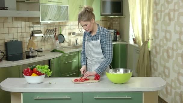 Young woman cutting paprika.