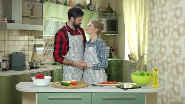 pár stojící v kuchyni.