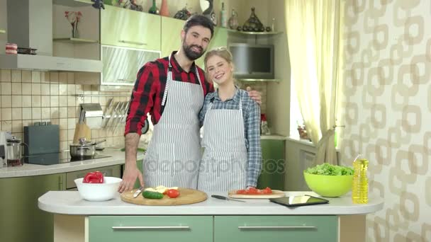 Young couple smiling, kitchen.