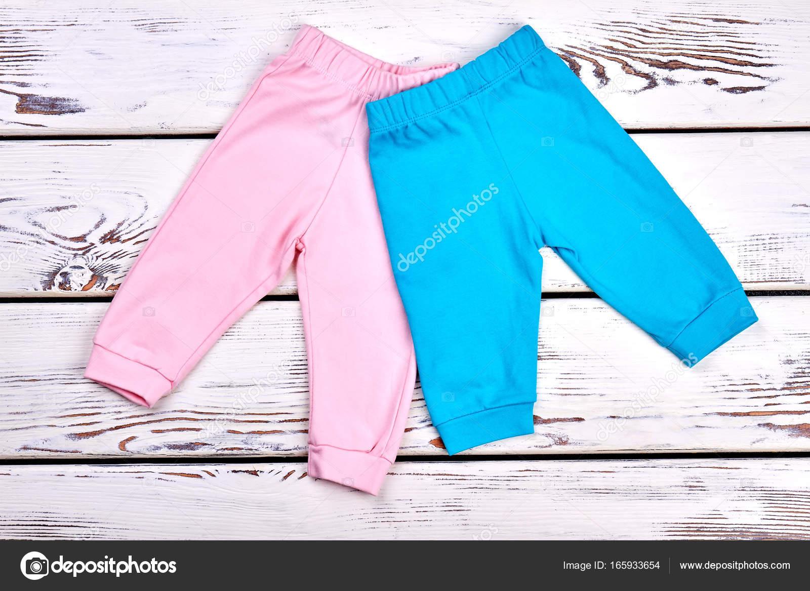 8168db604 Infantil niños y niñas colores pantalones sobre fondo blanco de madera. Ropa  ecológica niños en venta - imágenes  pantalon capri — Foto de Denisfilm —  Foto ...