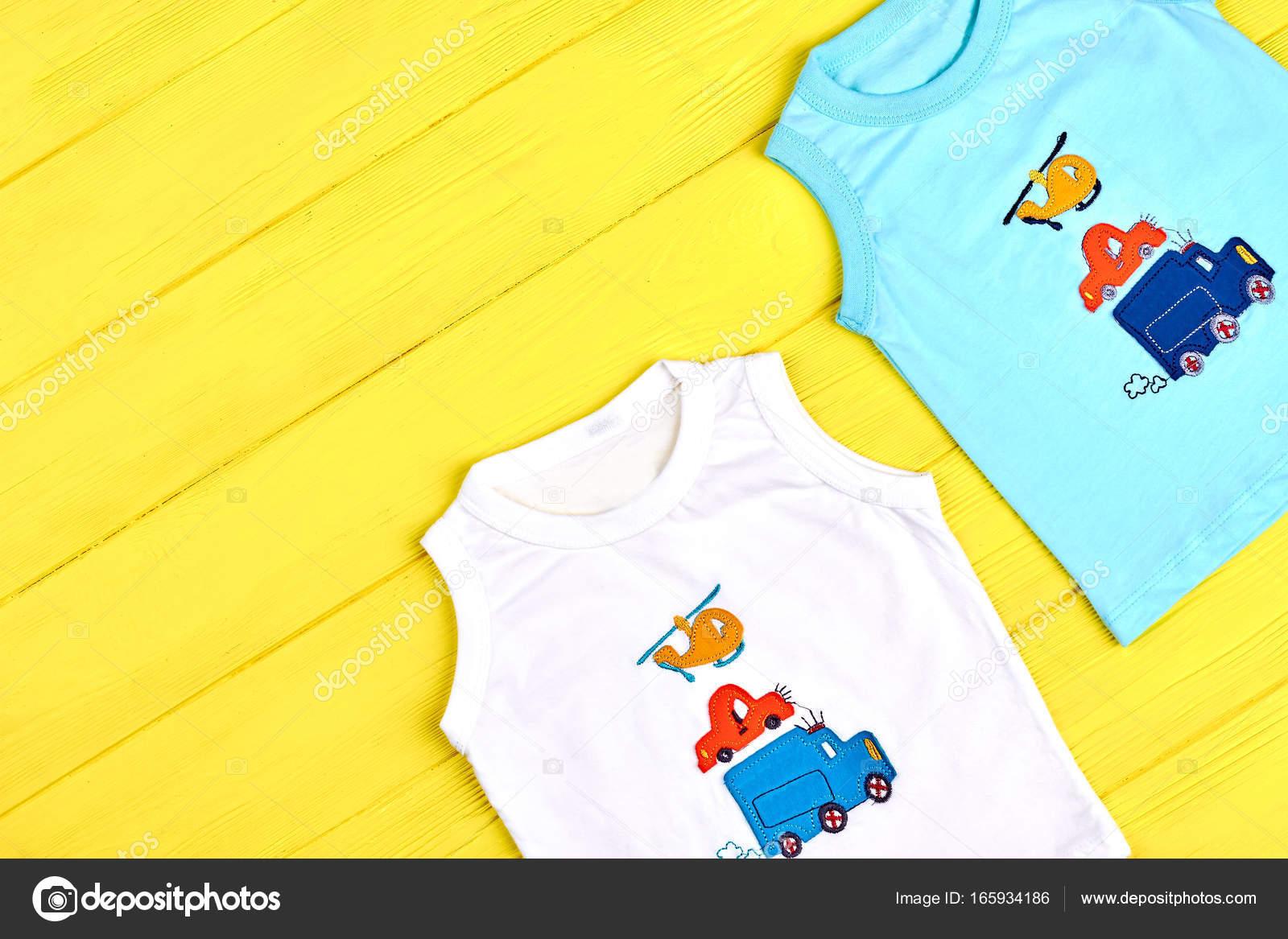 82c8b9cbd7748 D été pour bébés garçons vêtements colorés. Ensemble de tendance cartoon  t-shirts pour les garçons de bambin sur fond en bois jaune