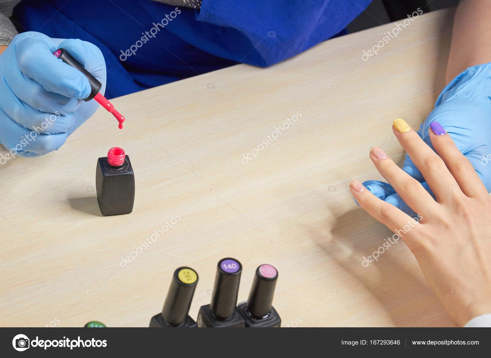 Manucure asiatique tient les mains du client dans un salon de