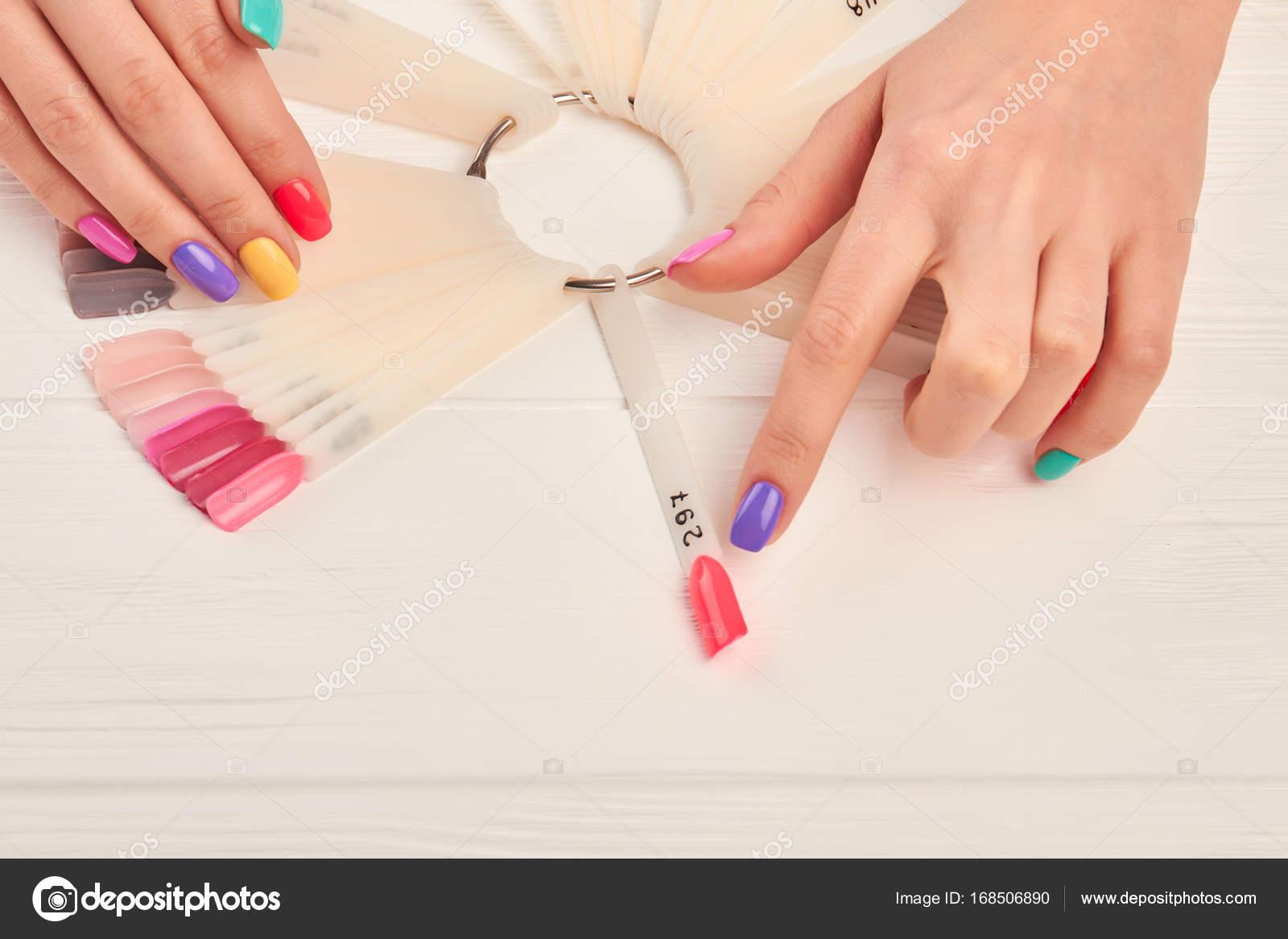 Female finger choosing nail color. — Stock Photo © Denisfilm #168506890