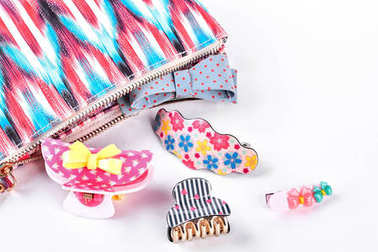 Hair clips next to patterned bag.