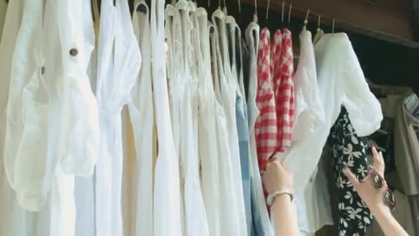 Oblečení na ramínkách, ženské ruce